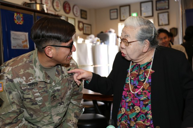 Staff Sgt. Karim Acosta, left, assigned to U.S. Army Medical Activity -- Japan, talks to Yukie Furukawa, a volunteer at Camp Zama's BG Crawford F. Sams U.S. Army Health Clinic, at a hail-and-farewell party Nov. 15 that recognized her 95th birthday.