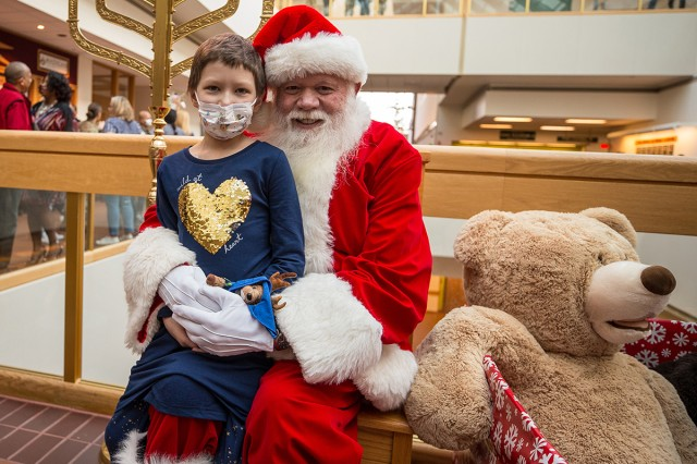 Keegan Bell, a patient at Madigan Army Medical Center's Pediatrics Clinic spends some time with Santa after she helped light the Christmas tree and menorah at a ceremony on Nov. 30.