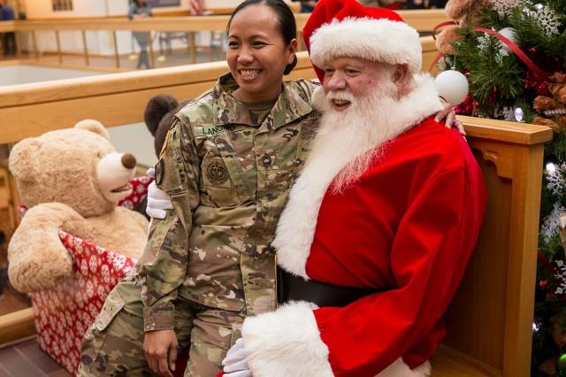 1st Sgt. Annalyn Langmo sits on Santa's lap at Madigan Army Medical Center's Christmas tree and menorah lighting ceremony on Nov. 30.