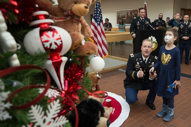 Madigan Commander Col. Thomas Bundt helps Keegan Bell, a patient in the Pediatrics Clinic light the Christmas tree at the tree and menorah lighting ceremony on Nov. 30.