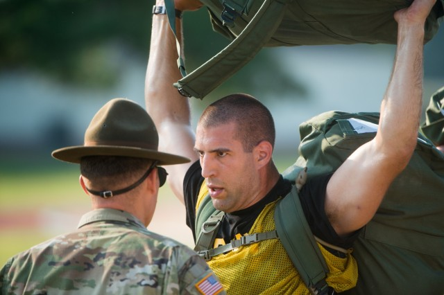 FORT BENNING, Ga. (July 13, 2018) - Spc. John Strezo from Burlington, Massachusetts, holds his duffel above his head. Initial entry trainees arrive at Echo Company, 2nd Battalion, 19th Infantry Regiment, on Fort Benning, Georgia, July 13, 2018, for the first day of the 22-week pilot program for One Station Unit Training for Infantry Soldiers. The new OSUT program included expanded weapons training, increased vehicle-platform familiarization, extensive combatives training, a 40-hour combat-lifesaver certification course, increased time in the field during both day and night operations and increased emphasis on drill and ceremony maneuvers. (U.S. Army photo by Patrick A. Albright, Fort Benning Maneuver Center of Excellence photographer)