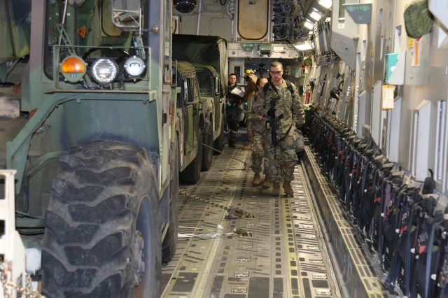 Soldiers load into a C-17 along with their vehicles during Rainier War 18 December 5 at McChord Airfield. Units from 593rd Expeditionary Sustainment Command provided personnel and vehicles to support the 62nd Airlift Wing's annual mobility training exercise.