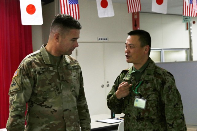 Sgt. Maj. Woody Carter, America's First Corps, talks with a Japanese Soldier at the icebreaker event leading to the start of Yama Sakaura 75 at Camp Higashi Chitose, Japan, Dec 6, 2018. Soldiers from America's First Corps, the 593rd Expeditionary Sustainment Command and other units joined the Northern Japan Army in an evening of food, conversation and cultural activities before the kickoff of the joint training exercise Yama Sakura. Yama Sakura, which means mountain cherry blossom, is a bilateral command post exercise with the Japan Ground Self-Defense Force in which U.S. and Japanese forces exchange ideas, techniques, military experience and exercise capabilities in defense of Japan. The exercise highlights the strength of the close, long-standing relationship the United States has with Japan and the JGSDF. U.S. Army photo by Sgt. Erica Earl