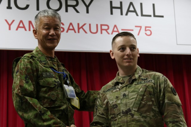 Sergeant Major of the Japan Ground Self-Defense Force, Warrant Officer Susumu Takahashi, greets a Soldier with America's First Corps at the icebreaker event leading to the start of Yama Sakaura 75 at Camp Higashi Chitose, Japan, Dec 6, 2018. In Japan, a warrant officer is equivalent to a command sergeant major. Soldiers from I Corps, the 593rd Expeditionary Sustainment Command and other units joined the Northern Japan Army in an evening of food, conversation and cultural activities  before the kickoff of the joint training exercise Yama Sakura. Yama Sakura, which means mountain cherry blossom, is a bilateral command post exercise with the Japan Ground Self-Defense Force in which U.S. and Japanese forces exchange ideas, techniques, military experience and exercise capabilities in defense of Japan. The exercise highlights the strength of the close, long-standing relationship the United States has with Japan and the JGSDF. U.S. Army photo by Sgt. Erica Earl