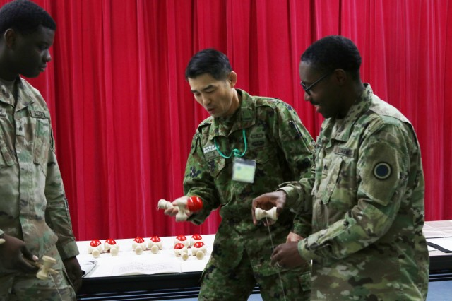Soldiers from the U.S. Army and the Northern Japan Army learn a traditional Japanese game at the icebreaker event leading to the start of Yama Sakaura 75 at Camp Higashi Chitose, Japan, Dec 6, 2018.  Soldiers from America's First Corps, the 593rd Expeditionary Sustainment Command and other units joined the Northern Japan Army in a variety of cultural activities before the kickoff of the joint training exercise Yama Sakura. Yama Sakura, which means mountain cherry blossom, is a bilateral command post exercise with the Japan Ground Self-Defense Force in which U.S. and Japanese forces exchange ideas, techniques, military experience and exercise capabilities in defense of Japan. The exercise highlights the strength of the close, long-standing relationship the United States has with Japan and the JGSDF. U.S. Army photo by Sgt. Erica Earl