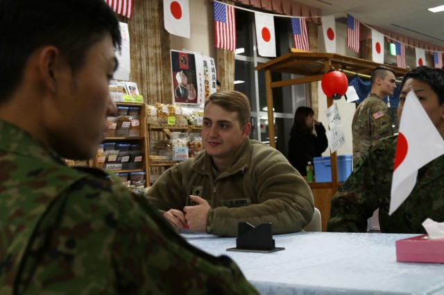 A Soldier with America's First Corps talks with Japanese Soldiers at the icebreaker event leading to the start of Yama Sakaura 75 at Camp Higashi Chitose, Japan, Dec 6, 2018.  Soldiers from America's First Corps, the 593rd Expeditionary Sustainment Command and other units joined the Northern Japan Army in in an evening of food, conversation and cultural activities before the kickoff of the joint training exercise Yama Sakura. Yama Sakura, which means mountain cherry blossom, is a bilateral command post exercise with the Japan Ground Self-Defense Force in which U.S. and Japanese forces exchange ideas, techniques, military experience and exercise capabilities in defense of Japan. The exercise highlights the strength of the close, long-standing relationship the United States has with Japan and the JGSDF. U.S. Army photo by Sgt. Erica Earl