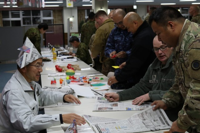 Soldiers with America's First Corps learn the Japanese art of origami at the icebreaker event leading to the start of Yama Sakaura 75 at Camp Higashi Chitose, Japan, Dec 6, 2018.  Soldiers from America's First Corps, the 593rd Expeditionary Sustainment Command and other units joined the Northern Japanese Army in an evening of food, conversation and cultural activities before the kickoff of the joint training exercise Yama Sakura. Yama Sakura, which means mountain cherry blossom, is a bilateral command post exercise with the Japan Ground Self-Defense Force in which U.S. and Japanese forces exchange ideas, techniques, military experience and exercise capabilities in defense of Japan. The exercise highlights the strength of the close, long-standing relationship the United States has with Japan and the JGSDF. U.S. Army photo by Sgt. Erica Earl