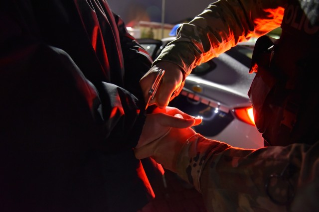 A U.S. Army Garrison Rheinland Pfalz military policeman with the Directorate of Emergency Services handcuffs a suspected shoplifter. According to the USAG RP Civilian Misconduct Office, individuals involved with law enforcement authorities of a host-nation government negatively reflect upon the United States and affect the success of its mission overseas.