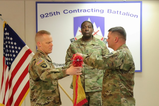 Lt. Col. Jessie Griffith, left, and Sgt. Maj. Timothy Higgs uncase the 925th Contracting Battalion colors as guidon bearer Master Sgt. Willie Signil looks on during a ceremony Nov. 28 at Fort Drum, New York.