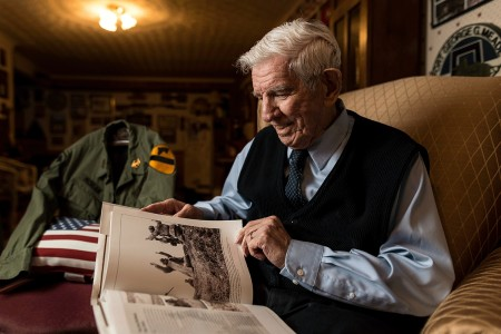 """Retired Command Sgt. Maj. Raymond Moran, affectionately known as the """"Old Soldier,"""" flips through a book on the Korean War during a portrait session in his home in Odenton, Md., while sharing stories about his military commitment to the U.S. Army and the U.S. Army Reserve during 65 years of service both as an enlisted Soldier and as a Department of the Army civilian. Moran served in Korea, Vietnam, Japan, Cambodia and during Desert Storm. He was instrumental in standing up the 220th Military Police Brigade, which has since become the 200th Military Police Command and is the largest military police organization in the U.S. Department of Defense."""