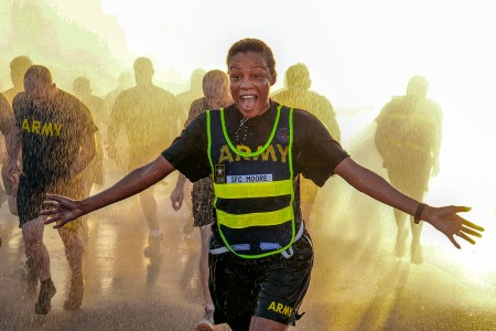 An Army Logistics University cadre member, wears an expression of surprise and joy while passing under a fountain of water as a refreshing feature of the Fort Lee's 243rd Army Birthday run, Fort Lee, Va., June 14, 2018.