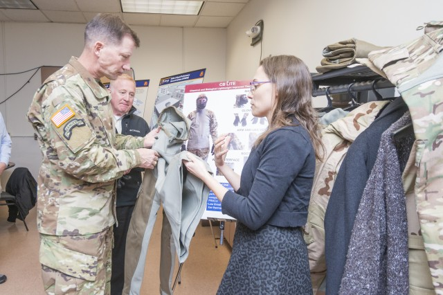 Brigadier General David M. Hodne, commandant of United States Army Infantry School at the Army Maneuver Center of Excellence, in Ft. Benning, Georgia, and director of the U.S. Army's Soldier Lethality Cross Functional Team, is briefed on different types of chemical biological protective garments by Dr. Natalie Pomerantz, a Research Chemical Engineer for the U.S. Army Research Development and Engineering Command Soldier Center during a recent visit to the Natick Soldier Systems Center in Natick, Mass., in order to learn more about recent efforts in technology development and human performance optimization.