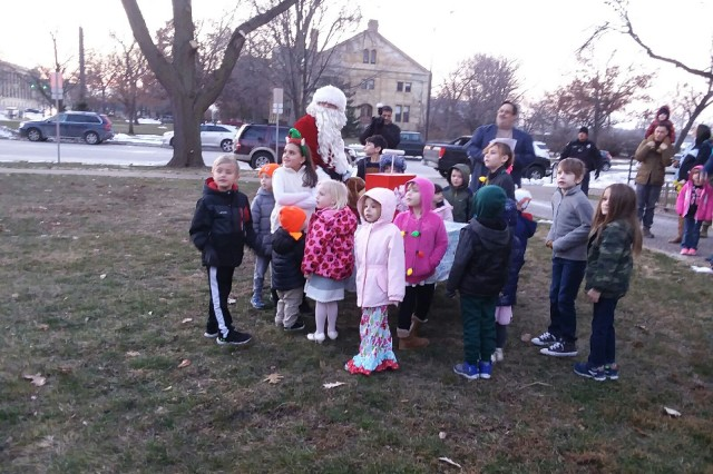 Children from Rock Island Arsenal's Child Development Center react to the event's festivities with Santa looking on at the 43rd annual Tree Lighting Ceremony held Dec. 7 outside and in Heritage Hall, Bldg. 60.