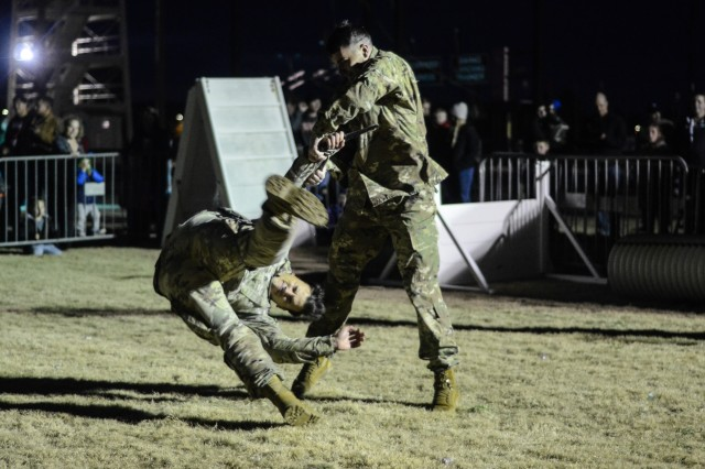 FORT BENNING, Ga. (Dec. 10, 2018) -- Soldiers of the Airborne and Ranger Training Brigade conduct a combatives demonstration. Families from across Fort Benning and the Chattahoochee Valley community gathered for a Benning holiday tradition Dec. 8 on Eubanks Field here. (U.S. Army photo by Megan Garcia, Maneuver Center of Excellence, Fort Benning Public Affairs)