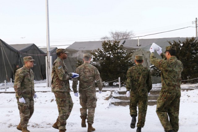 Soldiers from America's First Corps and the Japan Northern Army prepare to raise their respective nations' flags in a ceremony during Yama Sakura 75 at Camp Higashi-Chitose, Japan, Dec 11, 2018. American and Japanese forces raised the flags in unison to represent the teamwork involved in the exercise. Yama Sakura is a bilateral training exercise that strengthens America's alliance with the Japan Ground Self Defense Force and commitment to assisting in keeping the region secure. U.S. Army photo by Sgt. Erica Earl