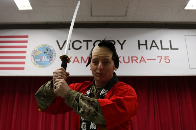 A Soldier from America's First Corps poses in traditional Samurai garb with a model katana at the icebreaker event leading to the start of Yama Sakaura 75 at Camp Higashi Chitose, Japan, Dec 6, 2018.  Soldiers from America's First Corps, the 593rd Expeditionary Sustainment Command and other units joined the Northern Japan Army in in an evening of food, conversation and cultural activities before the kickoff of the joint training exercise Yama Sakura. Yama Sakura, which means mountain cherry blossom, is a bilateral command post exercise with the Japan Ground Self-Defense Force in which U.S. and Japanese forces exchange ideas, techniques, military experience and exercise capabilities in defense of Japan. The exercise highlights the strength of the close, long-standing relationship the United States has with Japan and the JGSDF. U.S. Army photo by Sgt. Erica Earl