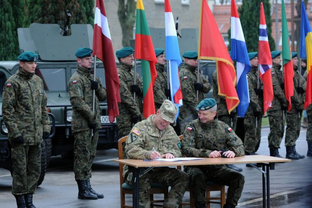 U.S. Army Lt. Gen. John Thomson, the commander of the NATO Allied Land Command, signs a dcoument certifying the Headquarters Multinational Division-North East during ANAKONDA-18 closing ceremony at the Headquarters Multinational Division - North East in Elblag, Poland, Dec. 6, 2018. AN-18 is the largest, periodic joint exercise organized by Poland. (U.S. Army National Guard photo by Sgt. 1st Class Craig Norton, 382nd Public Affairs Detachment/Released)