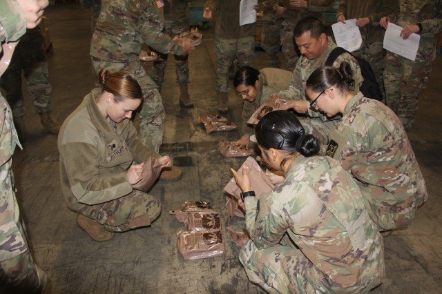 A group of soldiers work together to visually inspect MREs during an interactive training inspection day, Dec. 6.  The training event was hosted by Public Health Activity-Ft. Lewis.