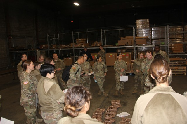 Spc. Matthew Reynolds provides a briefing to a group of soldiers who are gathered to inspect MREs on Dec. 6.  The training event was hosted by Public Health Activity-Ft. Lewis.