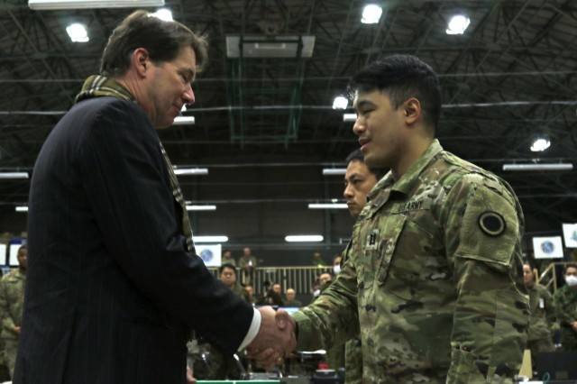 The U.S. Ambassador to Japan, Ambassador William Hagerty, presents a coin of recognition to Capt. Andrew Keopraseuth, America's First Corps, during Yama Sakura 75 at Camp Higashi-Chitose, Hokkaido, Japan, Dec 12 2018. Hagerty toured the camp and addressed the significance of the alliance between America and Japan. Yama Sakura is a bilateral training exercise that strengthens the relationship between the U.S. Army and the Japan Ground Self Defense Force through the exchange of ideas, tactics and techniques. U.S. Army photo by Sgt. Erica Earl
