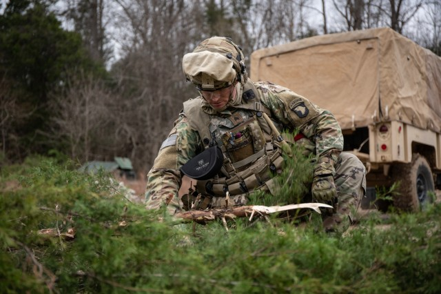 Sgt. Jared Chisholm from Company D. 21st Brigade Engineer Battalion, 3rd Brigade Combat Team, 101st Airborne Division (Air Assault) breaks apart a tree to be used as cover for his vehicle , Dec. 4 on Fort Knox, Kentucky. The cover was being used to hide the vehicles from possible enemy in the area as part of the brigade exercise. (US Army photo by Sgt. Patrick Kirby, 40th Public Affairs Detachment.)