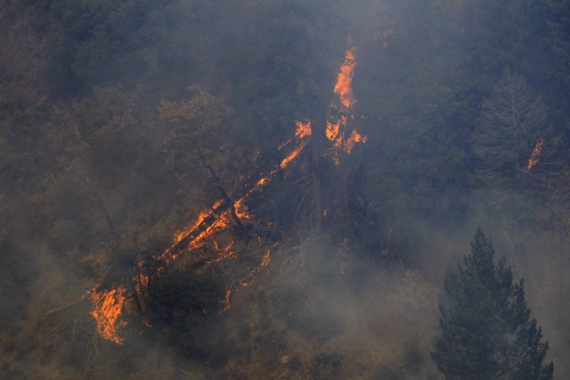 The Camp Fire burns trees and brush in the Feather River Canyon in Butte County, California, Nov. 16, 2018, as a U.S. Army UH-60M Black Hawk helicopter assigned to the 1st Assault Helicopter Battalion, 140th Aviation Regiment, California Army National Guard flies its first fire mission. The California National Guard provided four helicopters, including two of its new M-model Black Hawks, to help contain the fire.