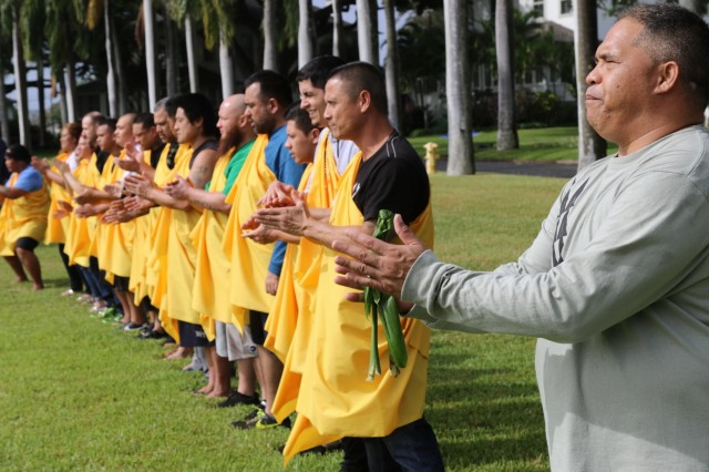 """FORT SHAFTER, Hawaii - Kanaka Oiwi, a group of traditional Hawaiian cultural practitioners, prepare to perform a traditional ceremony at Palm Circle at the promotion of their cousin, Sgt. 1st Class Justin Ka'ahanui, an U.S. Army Reserve Soldier and Native Hawaiian. """"There is deep history in this area, which is the Moanalua Valley, what was shared to me is it was training grounds for the arts of Hula, celebration of life, for the arts of Lua, warfare, for the arts of medicine, and Moanalua was a key place for training,"""" said Kupa Aina Nu'uanu Lenchanko, who participated in the ceremony. (Photo by Crista Mary Mack, 9th Mission Support Command)"""
