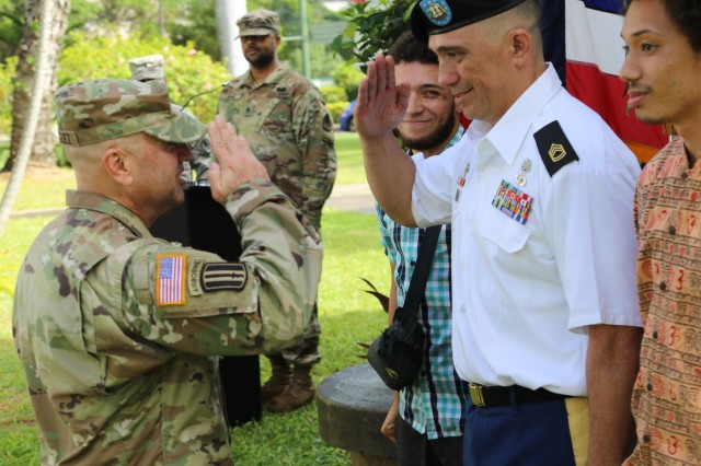 FORT SHAFTER, Hawaii - Commander of the 322nd Civil Affairs Brigade, Col. Rodriguez, salutes newly promoted civil affairs noncommissioned officer and medic Sgt. 1st Class Justin Ka'ahanui at his promotion as his sons Kolomana and Ku'ikaika stand by both sides.