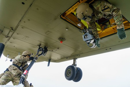 A CH-47 Chinook helicopter crew member with 1st Combat Aviation Brigade, 1st Cavalry Division, relays movement information to his pilots as a cannon crew member with 2nd Cavalry Regiment, works to secure his sling to the helicopter's cargo hook at an airfield near Grafenwoehr, Germany, March 6, 2018. Soldiers of both units came together to train and strengthen relationships while conducting sling load operations at Dynamic Front 18.