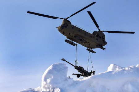A CH-47 Chinook helicopter delivers a 155mm howitzer to the Yukon Training Area, Alaska, March 7, 2018.