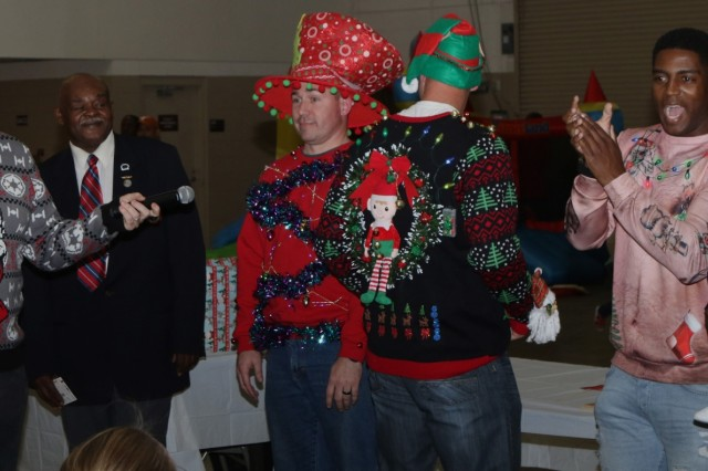 Soldiers and families with the Headquarters and Headquarters Battalion (rear)(provisional), XVIII Airborne Corps, compete in an ugly sweater contest during the unit's holiday party Dec. 7, 2018 at Fort Bragg, NC. The event brought soldiers and families together from across the unit to raise morale during the holiday season. (U.S. Army photo by Pvt. Nathaniel Gayle / 22nd Mobile Public Affairs Detachment )