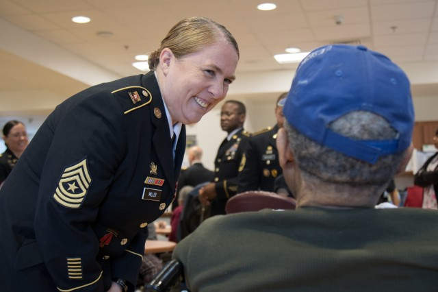 Sgt. Maj. Jane Miller, an acquisition, logistics, and technology contracting noncommissioned officer assigned to the 905th Contingency Contracting Battalion, converses with a local veteran at the Fayetteville Veterans Affairs medical center in Fayetteville, N.C., Dec. 5, 2018. Miller and the rest of the 905th volunteered their time to serve brunch and socialize with local veterans to give back to the surrounding community.