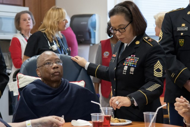 Master Sgt. Rosa Webb, an acquisition, logistics, and technology contracting noncommissioned officer assigned to the 905th Contingency Contracting Battalion, serves food to a local veteran at the Fayetteville Veterans Affairs medical center in Fayetteville, N.C., Dec. 5, 2018. Webb and the rest of the 905th volunteered their time to serve brunch and socialize with local veterans to give back to the surrounding community.