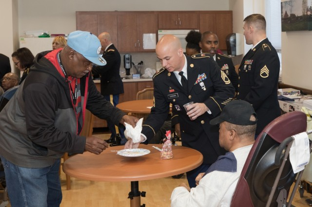 Soldiers with the 905th Contingency Contracting Battalion clear a veteran's plate at the Fayetteville Veterans Affairs Medical Center in Fayetteville, N.C., Dec. 5, 2018. The Soldiers of the 905th were at the Fayetteville VA Medical Center volunteering their time by serving local veterans brunch. (U.S. Army Photo by Pfc. Joshua Cowden / 22nd Mobile Public Affairs Detachment)