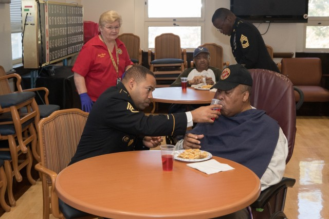 Sgt. 1st Class Shannon Booker, an acquisition, logistics, and technology contracting noncommissioned officer assigned to the 905th Contingency Contracting Battalion, assists a veteran in taking a drink at the Fayetteville Veterans Affairs Medical Center in Fayetteville, N.C., Dec. 5, 2018. The Soldiers of the 905th were at the Fayetteville VA Medical Center volunteering their time by serving local veterans brunch. (U.S. Army Photo by Pfc. Joshua Cowden / 22nd Mobile Public Affairs Detachment)