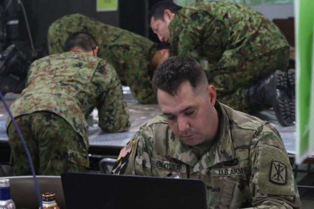 America's First Corps and Japan Northern Army Soldiers analyze maps and positioning strategy during Yama Sakura 75 at Camp Higashi-Chitose, Hokkaido, Japan, Dec. 13, 2018. Over the course of the week-long bilateral exercise, the U.S. Army and the Japan Ground Self Defense Force are working together in a simulation of the defense of Japan to strengthen the alliance and the capabilities of both countries' forces. Multiple sections are participating in the exercise, including signal, clerical, legal, medical and intelligence personnel. U.S. Army photo by Sgt. Erica Earl