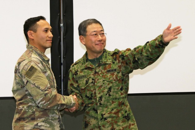 The Japan Northern Army Commanding General, Lt. Gen. Masato Taura, presents a coin to Capt. Tyle Tripop, an engineer operations officer with America's First Corps America's First Corps, in the Hero of the Battle portion of a bilateral meeting during Yama Sakura 75 at Camp Higashi-Chitose, Hokkaido, Japan, Dec 12, 2018. The Hero of the Battle is a daily recognition of Soldiers who contributed strongly to the effort of the exercise. Yama Sakura is a bilateral event with the U.S. Army and the Japan Ground Self Defense Force that simulates the defense of Japan and strengthens the alliance between the two Armies. U.S. Army photo by Sgt. Erica Earl