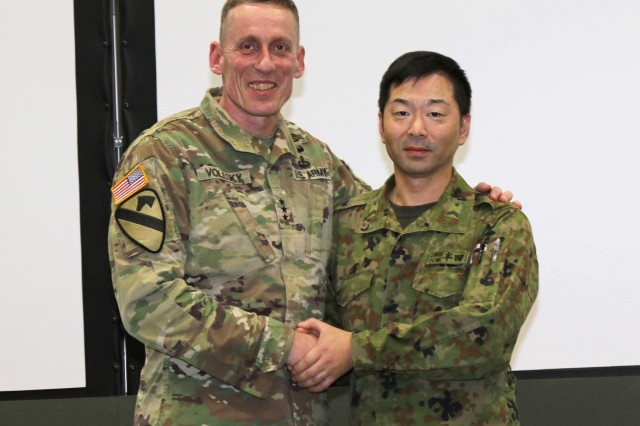 America's First Corps Commanding General, Lt. Gen. Gary Volesky, presents a coin to Sgt. First Class Hiroyuki Handa of the Japan Northern Army in the Hero of the Battle portion of a bilateral meeting during Yama Sakura 75 at Camp Higashi-Chitose, Hokkaido, Japan, Dec 12, 2018. The Hero of the Battle is a daily recognition of Soldiers who contributed strongly to the effort of the exercise. Yama Sakura is a bilateral event with the U.S. Army and the Japan Ground Self Defense Force that simulates the defense of Japan and strengthens the alliance between the two Armies. U.S. Army photo by Sgt. Erica Earl