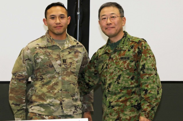 The Japan Northern Army Commanding General, Lt. Gen. Masato Taura, presents a coin to Capt. Tyle Tripop, an engineer operations officer with America's First Corps in the Hero of the Battle portion of a bilateral meeting during Yama Sakura 75 at Camp Higashi-Chitose, Hokkaido, Japan, Dec 12, 2018. The Hero of the Battle is a daily recognition of Soldiers who contributed strongly to the effort of the exercise. Yama Sakura is a bilateral event with the U.S. Army and the Japan Ground Self Defense Force that simulates the defense of Japan and strengthens the alliance between the two Armies. U.S. Army photo by Sgt. Erica Earl