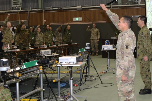 "Capt. Tyle Tripop, an engineer operations officer with America's First Corps, and Sgt. First Class Hiroyuki Handa, Japan Northern Army, lead Soldiers from the U.S. Army and the Japan Northern Army in the victory cry ""Onward together!"" at Yama Sakura 75 at Camp Higashi-Chitose, Hokkaido, Japan, Dec 12, 2018, in the Hero of the Battle portion of a bilateral meeting. The Hero of the Battle is a daily recognition of Soldiers who contributed strongly to the effort of the exercise. Yama Sakura is a bilateral event with the U.S. Army and the Japan Ground Self Defense Force that simulates the defense of Japan and strengthens the alliance between the two Armies. U.S. Army photo by Sgt. Erica Earl"