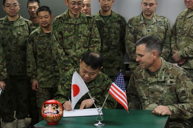 Col. Mikio Takeshima, M.D. Northern Army Headquarters surgeon, Japan Ground Self Defense Force (left) signs a medical support agreement with Col Robert Forsten, D.O., America's First Corps surgeon, during Yama Sakura 75 at Camp Higashi-Chitose, Hokkaido, Japan, Dec. 10, 2018.  This agreement allows mutual medical support between the forces as needed, including patient evacuation, casualty treatment and patient logistics, during the course of the exercise. Yama Sakura is a bilateral exercise that combines the capabilities of the U.S. Army and the JGSDF and solidifies the working relationship between the forces. U.S. Army photo by Sgt. Erica Earl