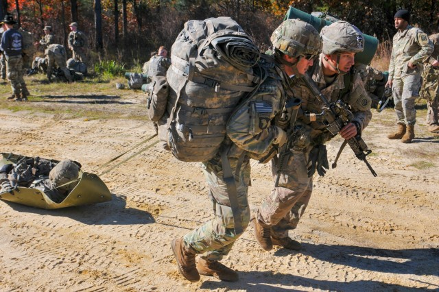 Two Spur Candidates from the 82nd Airborne Division drag a weighted litter during a lane evaluating their medical knowledge Tuesday, November 26 on Fort Bragg. The candidates were participating in a Spur Ride honoring the heritage of the 73rd Cavalry Regiment by testing the candidates' grit and determination over a 36-hour period where they were evaluated on their knowledge of regimental history, tactics, medical skills and airborne proficiency.