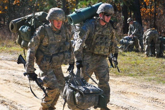 Two Spur Candidates from the 82nd Airborne Division carry a weighted rucksack while moving between evaluation lanes Tuesday, November 26 on Fort Bragg. The candidates were participating in a Spur Ride honoring the heritage of the 73rd Cavalry Regiment by testing the candidates' grit and determination over a 36-hour period where they were evaluated on their knowledge of regimental history, tactics, medical skills and airborne proficiency.