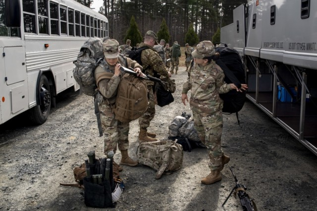 U.S. Army Reserve military police Soldiers and U.S. Army Reserve combat medic from the 805th Military Police Company unload gear from the bus at Camp Butner, N.C., Dec. 7, 2018.