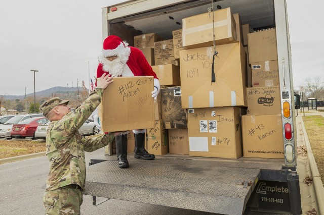 Santa hands the first box of presents to Anniston Army Depot Commander Col. Joel Warhurst as ANAD employees deliver gifts for 180 children to the Calhoun County Department of Human Resources Dec. 13, 2018.