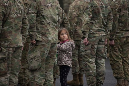 A little girl holds her father's hand during a Family Safety Day parade dupported by the USO and other organizations, March 16, 2018, at U.S. Army Garrison Wiesbaden, Germany.