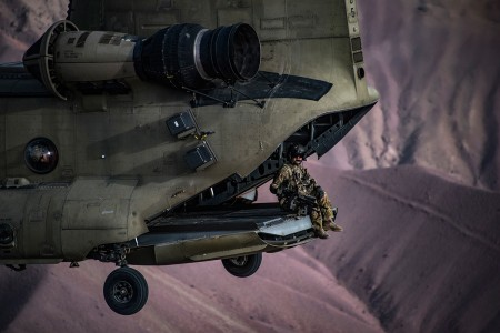 A U.S. Army Task Force Brawler CH-47F Chinook flight engineer sits on the ramp while conducting a training exercise with a Guardian Angel team assigned to the 83rd Expeditionary Rescue Squadron at Bagram Airfield, Afghanistan, March 26, 2018. The Army crews and Air Force Guardian Angel teams conducted the exercise to build teamwork and procedures as they provide joint personnel recovery capability, aiding in the delivery of decisive air power for U.S. Central Command.