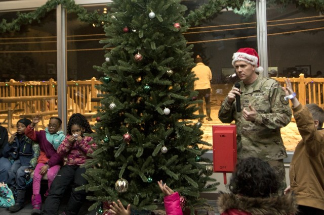 Col. Sean Fisher (right), U.S. Army Garrison Alaska commander, picks out a service member's child to help turn on the Birch Hill Ski and Snowboard Area Christmas tree during the 2018 Holiday Party on Dec. 7. The annual event is held to celebrate the holidays with the Tree Lighting Ceremony, a Santa Shred where skiers and snowboarders race down the slope dressed as Santa Claus, ice sculptures and a reindeer. (Photo by Daniel Nelson, U.S. Army Garrison Alaska Fort Wainwright Public Affairs)