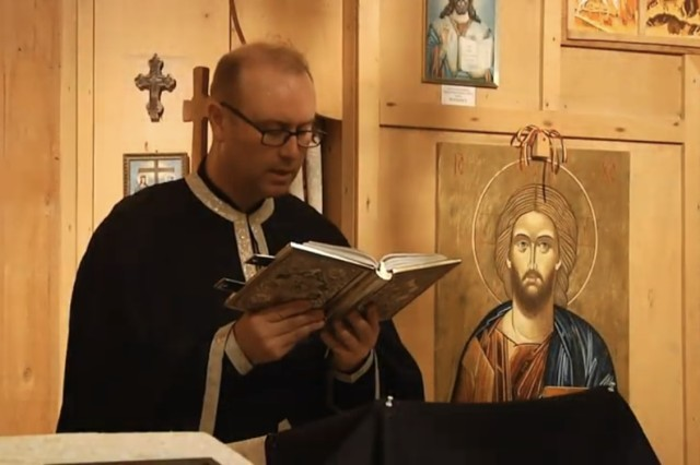 Chaplain (Capt.) George Oanca reads aloud from Scripture.