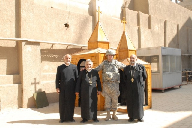 Chaplain (Capt.) Oanca stands with Eastern Orthodox priests in front of a shrine during his deployment to Baghdad, Iraq.